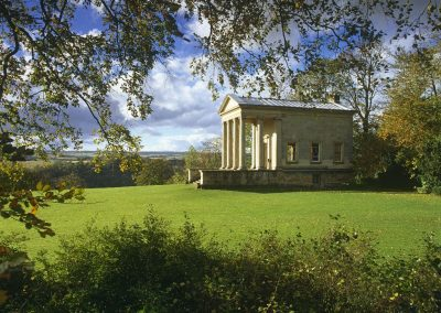 The Ionic Temple at Rievaulx built by Thomas Duncombe II in 1758 framed by trees and shrubs, Helmsley, North Yorkshire