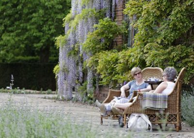 Visitors enjoying afternoon tea in the garden at Goddards, an arts and crafts style house in North Yorkshire.